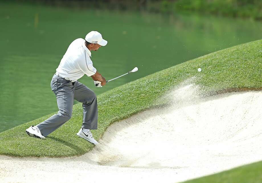 Tiger Woods hits a shot from the sand on the 12th hole, where he had one of his two double bogeys on the back nine, to go along with a triple bogey. Photo: Andy Lyons, Getty Images