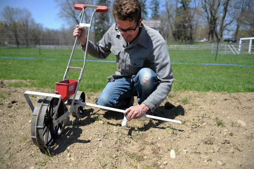 Thad Simerly adjusts a seed planter at the farm where he and his wife are renting land on Thursday, April 25, 2013 in Red Hook, NY. The couple is in their first season of farming, after moving to the Hudson Valley from NYC. (Paul Buckowski / Times Union)