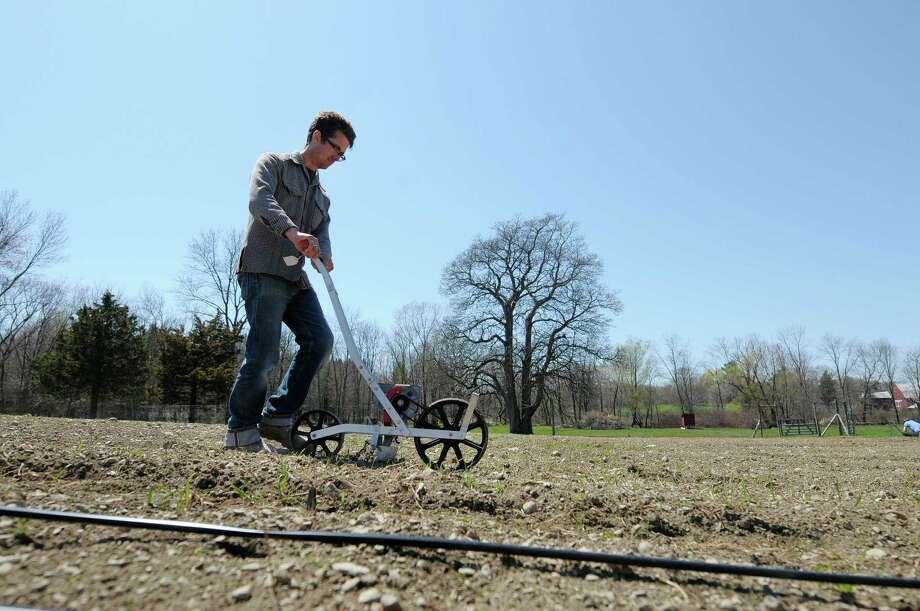 Thad Simerly plants seeds at the farm where he and his wife are renting land on Thursday, April 25, 2013 in Red Hook, NY.  The couple is in their first season of farming, after moving to the Hudson Valley from NYC.    (Paul Buckowski / Times Union) Photo: Paul Buckowski