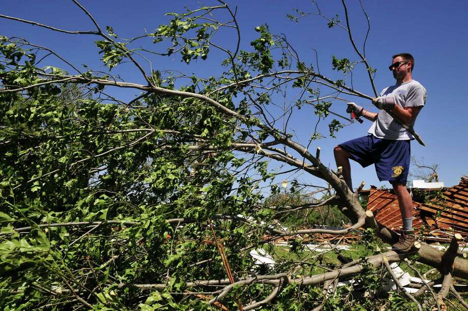 Josh Hill, a volunteer with Grace Chapel in Englewood, Colo., helps to clear downed branches from Angela and Wade Burleson's yard in El Reno Okla. on Saturday June 1, 2013 after their home was destroyed by one of the tornados that swept through Central Okla. on Friday. (AP Photo/Nick Oxford) Photo: Nick Oxford