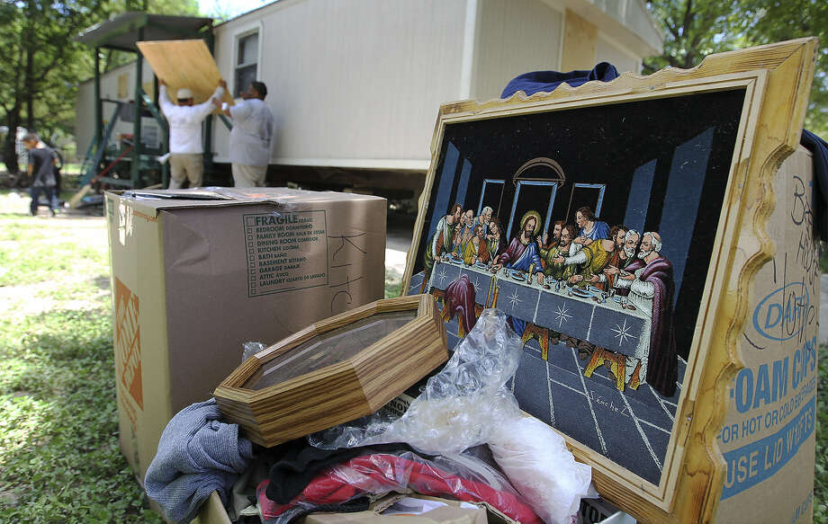 A painting of the Last Supper is among the items salvaged from the home of Jose Guerrero at Big Tree Trailer City, which was inundated by the floodwaters. Residents were told they had to leave their homes. Photo: Photos By Kin Man Hui / San Antonio Express-News