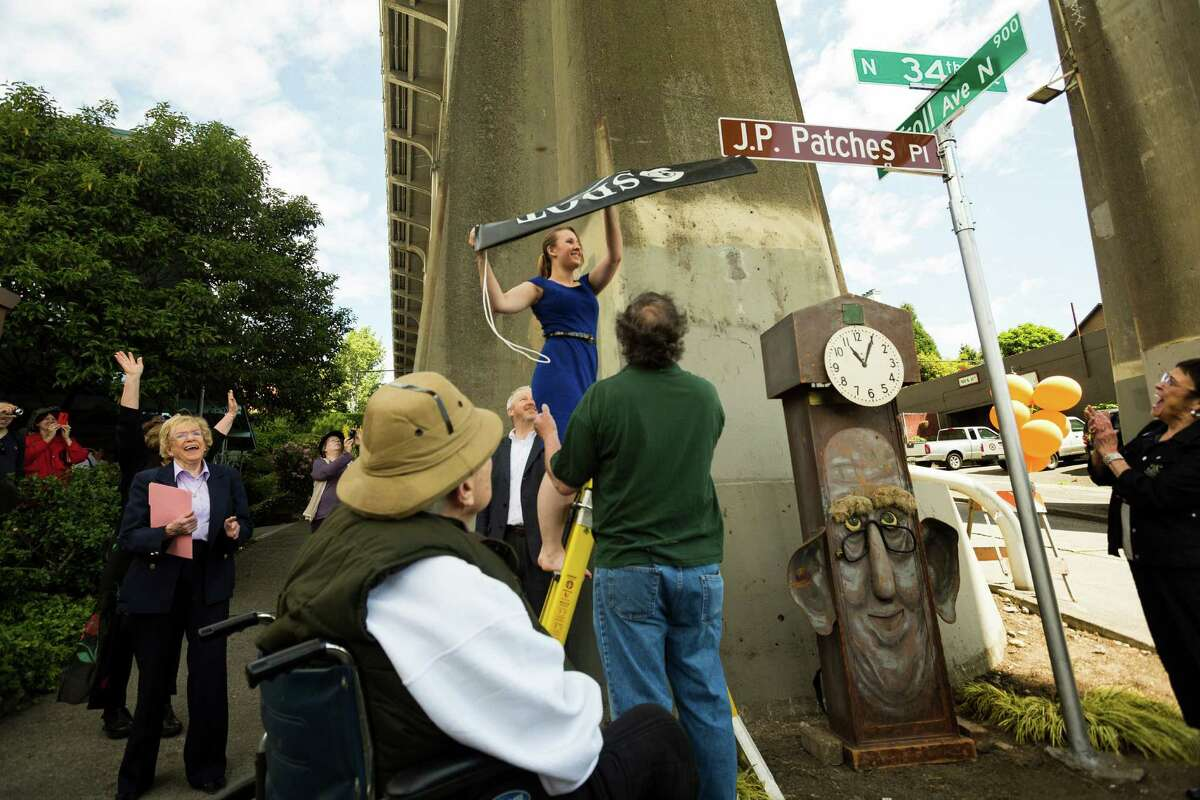Chris Wedes' granddaughter Christina Frost, in blue, pulls off the sign cover at the J.P. Patches Place street naming event Saturday, June 1, 2013, at the History House of Greater Seattle in Fremont. The newly named street section is located on North 34th Street between Fremont Avenue North and Troll Way North, and runs directly in front of the J.P. Patches and Gertrude