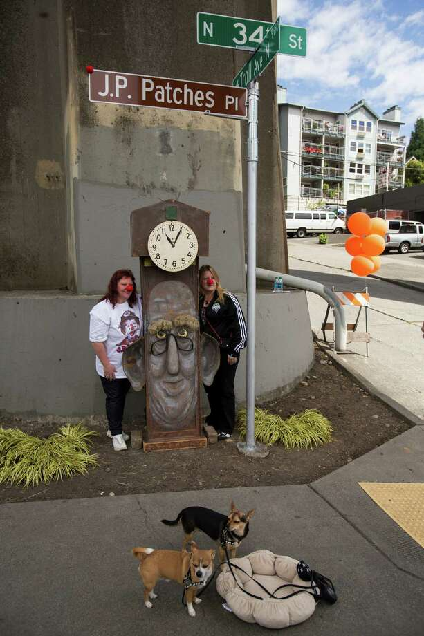 """Tamara Schemp, left, and friend Marti Kirby, right, stand near the unveiled J.P. Patches Place street sign to get their picture taken Saturday, June 1, 2013, at the History House of Greater Seattle in Fremont. The newly named street section is located on North 34th Street between Fremont Avenue North and Troll Way North, and runs directly in front of the J.P. Patches and Gertrude """"Late for the Interurban"""" statue in Fremont. Photo: JORDAN STEAD, SEATTLEPI.COM / SEATTLEPI.COM"""