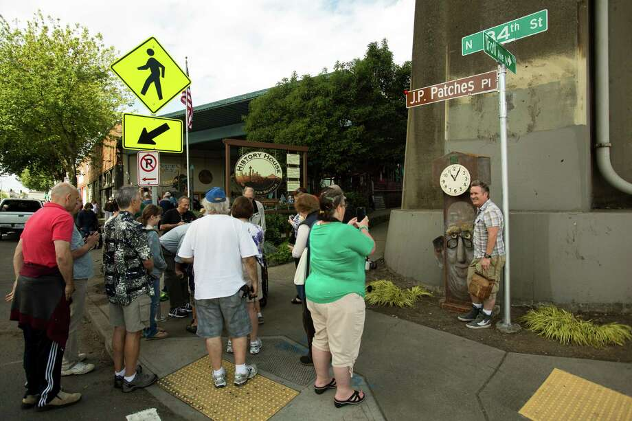 "Event attendees gather near the unveiled J.P. Patches Place street sign to take pictures Saturday, June 1, 2013, at the History House of Greater Seattle in Fremont. The newly named street section is located on North 34th Street between Fremont Avenue North and Troll Way North, and runs directly in front of the J.P. Patches and Gertrude ""Late for the Interurban"" statue in Fremont. Photo: JORDAN STEAD, SEATTLEPI.COM / SEATTLEPI.COM"