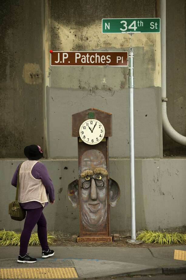 "A view of ""Grandpa Tick Tock"" under the J.P. Patches Place street sign Saturday, June 1, 2013, at the History House of Greater Seattle in Fremont. The newly named street section is located on North 34th Street between Fremont Avenue North and Troll Way North, and runs directly in front of the J.P. Patches and Gertrude ""Late for the Interurban"" statue in Fremont. Photo: JORDAN STEAD, SEATTLEPI.COM / SEATTLEPI.COM"