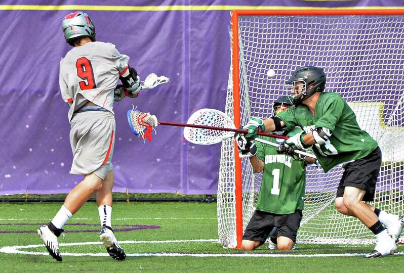 Niskayuna's #9 Luke Goldstock scores past Cornwall goalie Victor Ramos and defender John Roth, at ri