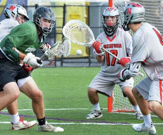 Niskayuna  goalie # 17 Evan Quinn, center, guards goal during their lacrosse state tournament game a