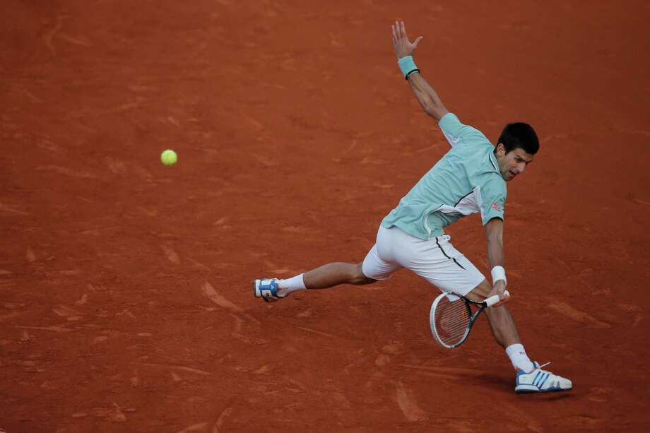 Serbia's Novak Djokovic returns against Bulgaria's Grigor Dimitrov in their third round match at the French Open tennis tournament, at Roland Garros stadium in Paris, Saturday, June 1, 2013. Djokovic won in three sets. (AP Photo/Michel Spingler) Photo: Michel Spingler