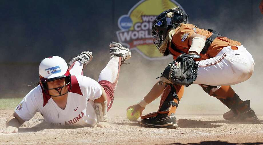 Oklahoma's Brittany Williams reaches to score while Texas catcher Mandy Ogle, a New Braunfels Canyon grad, tries to make a tag in the third inning. The Longhorns jumped out to a 2-0 lead but couldn't hold it. Photo: Nate Billings / The Oklahoman