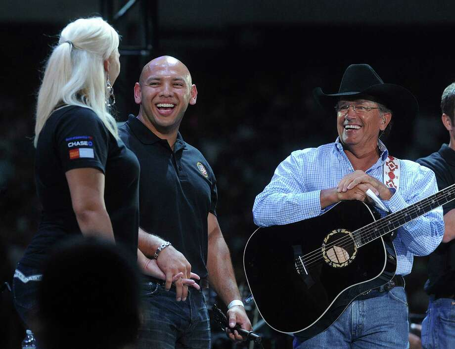 "Marine Corps veteran Jose Sanchez, who was wounded in Afghanistan, smiles at his wife, Angela, after country music legend George Strait, right, announced that they were being presented with a home by the Military Warrior Support Foundation's ""Homes 4 Wounded Warriors"" program during ""The Cowboy Rides Away"" tour in the Alamodome on Saturday, June 1, 2013. Photo: San Antonio Express-News / San Antonio Express-News"