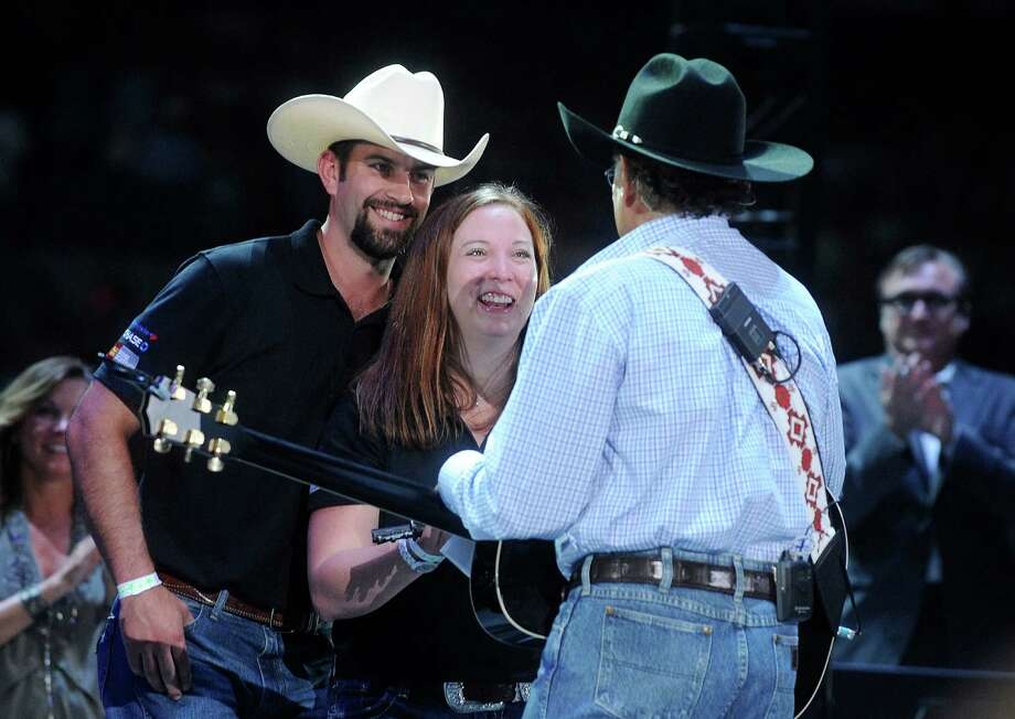 "John Faulkenberry, left, and his wife, Sarah, react as country music singer George Strait presents them with the key to a house given by the Military Warrior Support Foundation's ""Homes 4 Wounded Warriors"" program during a concert in the Alamodome on Saturday, June 1, 2013. John Faulkenberry was wounded in Afghanistan. Photo: Billy Calzada, San Antonio Express-News / San Antonio Express-News"