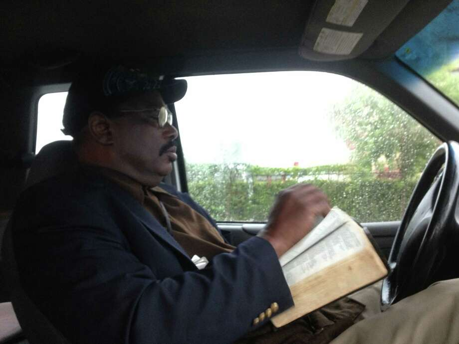 Reverend Robert M. Gilmore with Real Urban Ministries reads a Bible in his vehicle while waiting for the rain to stop before a scheduled prayer service at the scene of fire which killed four HFD firefighters on Friday. Photo: James Nielsen/Chronicle