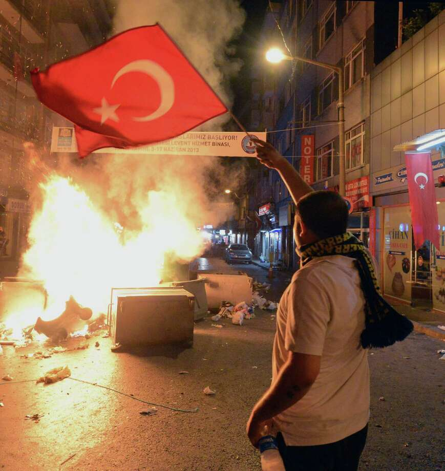 In this photo taken late Saturday, June 1, 2013, a demonstrator waves a national flag as Turkish protesters clash with riot police near the former Ottoman palace, Dolmabahce, where Turkey's Prime Minister Recep Tayyip Erdogan maintains an office in Istanbul, Turkey. Protests in Istanbul, Ankara and several other Turkish cities appear to have subsided Sunday, after days of fierce clashes following a police crackdown on a peaceful gathering as protesters denounced what they see as Prime Minister Recep Tayyip Erdogan's increasingly authoritarian style. Photo: AP