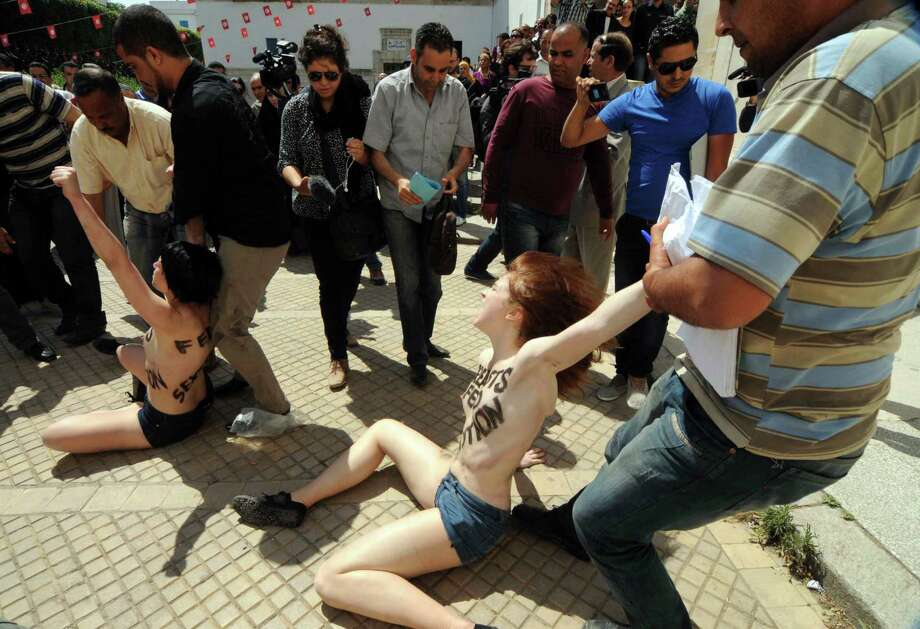 Activists from the women's movement FEMEN are arrested by plainclothes police officers while staging a protest against the jailing of a Tunisian member in Tunis, Tunisia, Wednesday, May 29, 2013. Three foreign activists disrobed in front of the Ministry of Justice to protest against the jailing of a Tunisian member of the Ukrainian feminist group FEMEN, quickly attracting a crowd of offended Tunisians before the three women were hustled away by police. Photo: AP