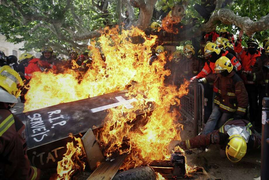 "Firefighters burn a mock coffin bearing the words ""RIP Public Services"", during a protest against austerity measures in front of the Catalunya Parliament in Barcelona, Spain, Wednesday, May 29, 2013. The European Union moved away from its focus on tough austerity Wednesday when it gave France, Spain and four other member states more time to bring their budget deficits under control to support their economies. Photo: AP"