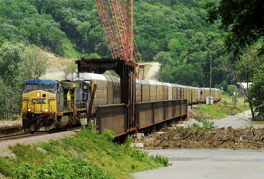 A CSX freight train towing a load of auto racks pulls into Osage City, Missouri, as storm and flood debris collects at the base of the soon-to-be-replaced Osage River rail bridge on the east edge of town on Saturday, June 1, 2013 in Osage City, Mo. Photo: AP