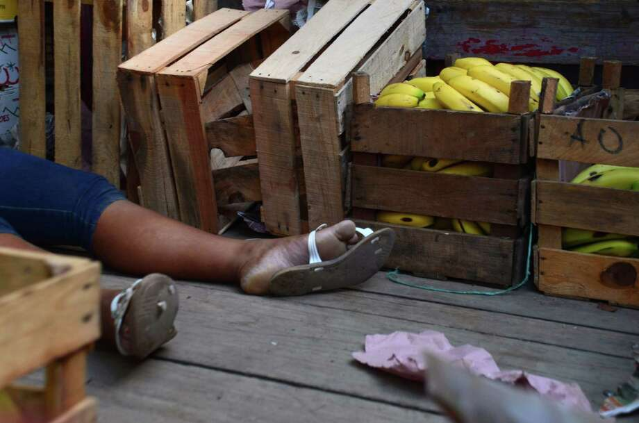 The body of a woman lies next to her crates of bananas at the main market in Acapulco, Mexico, Saturday, June 1, 2013. The women was shot to death while she and her family were unloading merchandise to sell at the market. Four of her family members also died in the attack, and two were injured, according to police. The resort city of Acapulco has been hit by increased violence as drug gangs battle for control of the region. Photo: AP