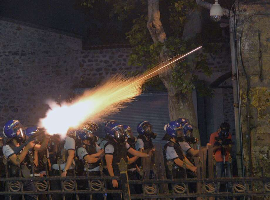 CORRECTS  DAY TO SATURDAY In this photo taken late Saturday, June 1, 2013, riot police fire, as they clash with protestors, near the former Ottoman palace, Dolmabahce, where Turkey's Prime Minister Recep Tayyip Erdogan maintains an office in Istanbul, Turkey. Protests in Istanbul, Ankara and several other Turkish cities appear to have subsided Sunday, after days of fierce clashes following a police crackdown on a peaceful gathering as protesters denounced what they see as Prime Minister Recep Tayyip Erdogan's increasingly authoritarian style. Photo: AP