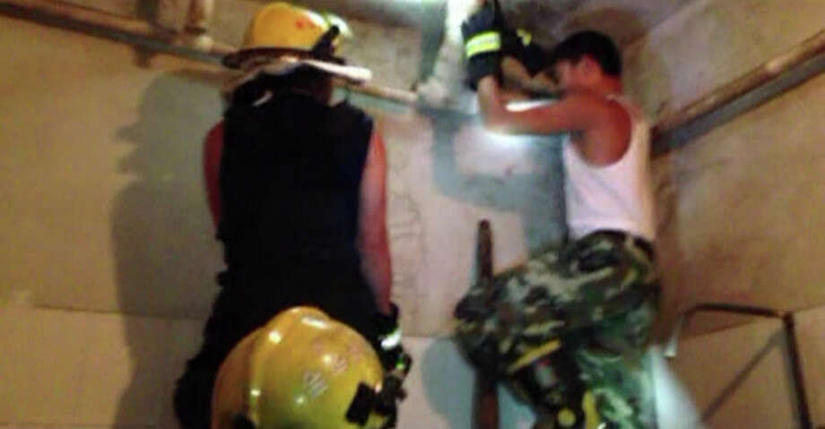 In this still image taken from video from Saturday May 25, 2013, a firefighter attempts to remove a section of a sewage pipe where a newborn baby appears trapped, in Pujiang in east China's Zhejiang province. Chinese firefighters have rescued a newborn boy from a sewer pipe below a squat toilet, sawing out an L-shaped section and then delicately dismantling it to free the trapped baby, who greeted the rescuers with cries. A tenant heard the baby's sounds in the public restroom of a residential building in Zhejiang province in eastern China on Saturday and notified authorities, according to the state-run news site Zhejiang News. A video of the two-hour rescue that followed was broadcast widely on Chinese news programs and websites late Monday and Tuesday. (AP Photo) Photo: AP
