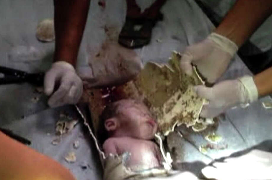 In this still image taken from video from Saturday May 25, 2013, rescue workers cut away parts of a sewage pipe where a newborn baby was trapped in Pujiang in east China's Zhejiang province. Chinese firefighters have rescued a newborn boy from a sewer pipe below a squat toilet, sawing out an L-shaped section and then delicately dismantling it to free the trapped baby, who greeted the rescuers with cries. A tenant heard the baby's sounds in the public restroom of a residential building in Zhejiang province in eastern China on Saturday and notified authorities, according to the state-run news site Zhejiang News. A video of the two-hour rescue that followed was broadcast widely on Chinese news programs and websites late Monday and Tuesday. (AP Photo) Photo: AP