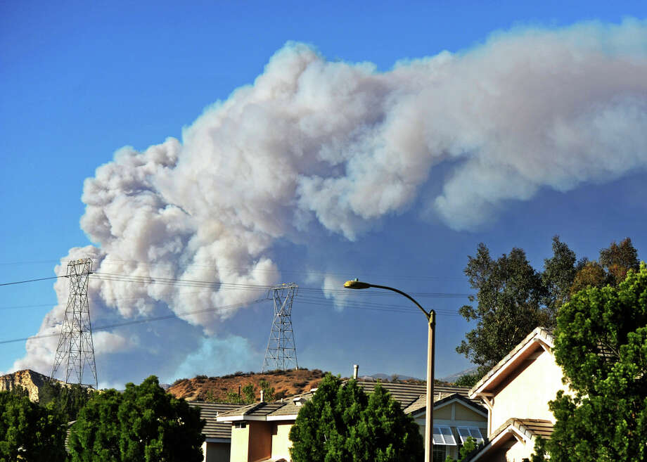 Smoke from the Powerhouse Fire is visible from the Saugus neighborhood of Santa Clarita, Calif., Thursday, May 30, 2013. The fire in the Angeles National Forest surged to 1,000 acres after burning for about four hours, the U.S. Forest Service said, sending out big clouds of black smoke amid temperatures in the high 80s and winds gusting at more than 20 mph. (AP Photo/Santa Clarita Valley Signal, Jonathan Pobre) Photo: AP