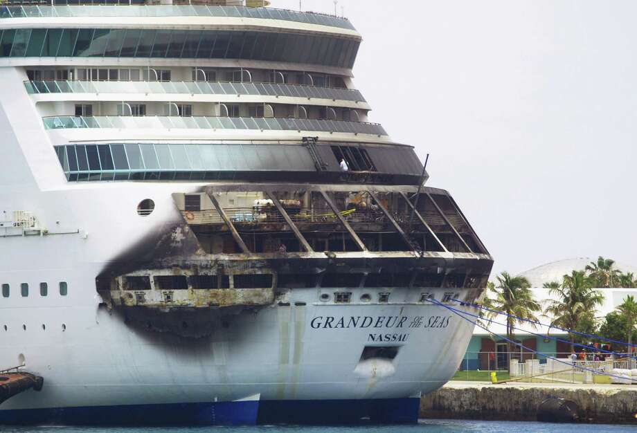 The fire-damaged exterior of Royal Caribbean's Grandeur of the Seas cruise ship is seen while docked in Freeport, Grand Bahama island, Monday, May 27, 2013. Royal Caribbean said the fire occurred early Monday while on route from Baltimore to the Bahamas on the mooring area of deck 3 and was quickly extinguished. All 2,224 guests and 796 crew were safe and accounted for. Photo: AP