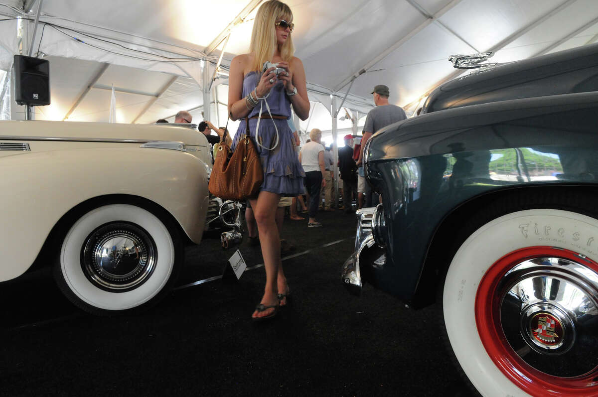 Rachael Teutul fis framed by a 1940 Chrysler New Yorker Highlander and a 1941 Cadillac Series 62 before they are auctioned as the British based auction house Bonhams hosts the annual auction of rare and classic cars at the Greenwich Concours d'Elegance at Roger Sherman Baldwin Park in Greenwich, Conn., June 2, 2013.