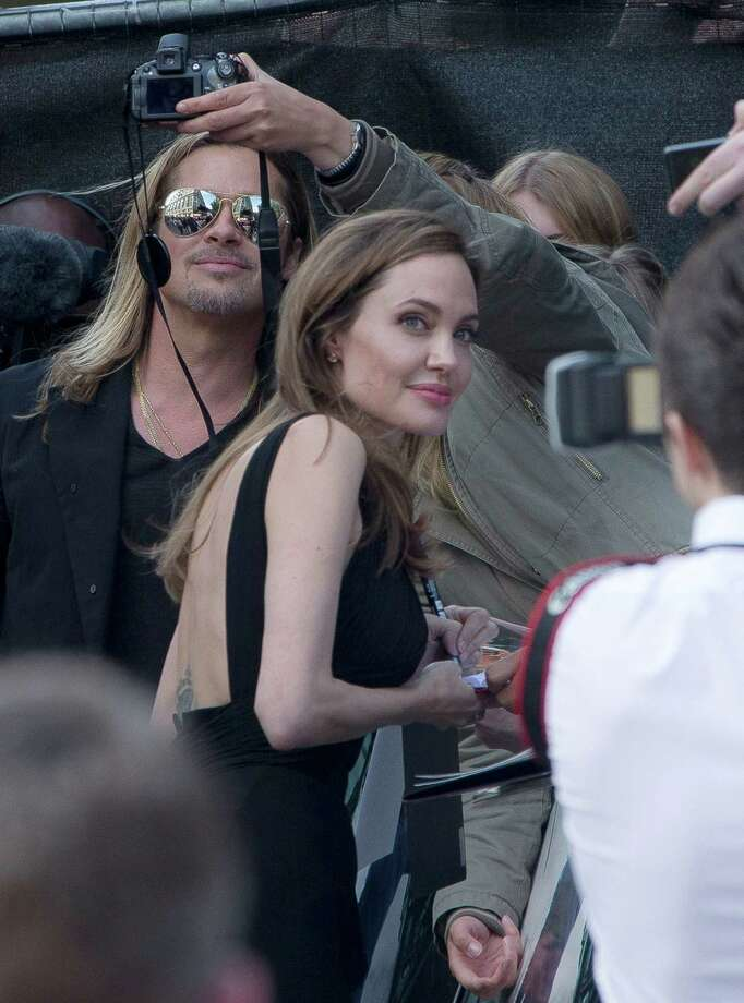 Brad Pitt and Angelina Jolie pose with fans as they arrive for the World Premiere of World War Z  at a central London cinema, Sunday, June 2, 2013. Photo: AP