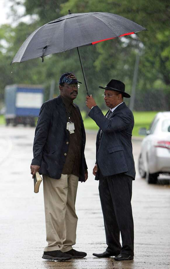 Real Urban Ministries Reverend Robert M. Gilmore left, and Southwest Baptist Church Pastor Rickie Bradshaw right, wait in the rain prior to a prayer service at the scene of Friday's deadly fire which claimed the lives of four Houston Fire Department firefighters Sunday, June 2, 2013, in Houston. Photo: James Nielsen, Houston Chronicle / © 2013  Houston Chronicle