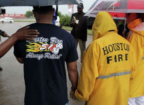 A woman places her hand on HFD station 51 firefighter George Saldana during to a prayer service at the scene of Friday's deadly fire which claimed the lives of four Houston Fire Department firefighters Sunday, June 2, 2013, in Houston. Photo: James Nielsen, Houston Chronicle / © 2013  Houston Chronicle