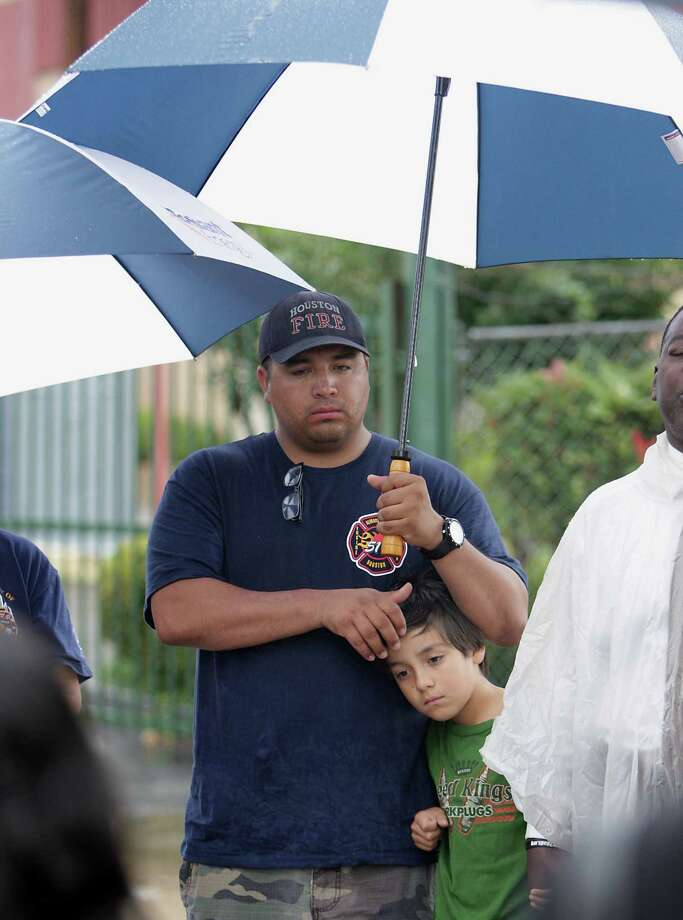 Houston Fire Department station 51 firefighter George Saldana, Sr. left, holds his son George Saldana, Jr. during to a prayer service at the scene of Friday's deadly fire which claimed the lives of four Houston Fire Department firefighters Sunday, June 2, 2013, in Houston. Photo: James Nielsen, Houston Chronicle / © 2013  Houston Chronicle