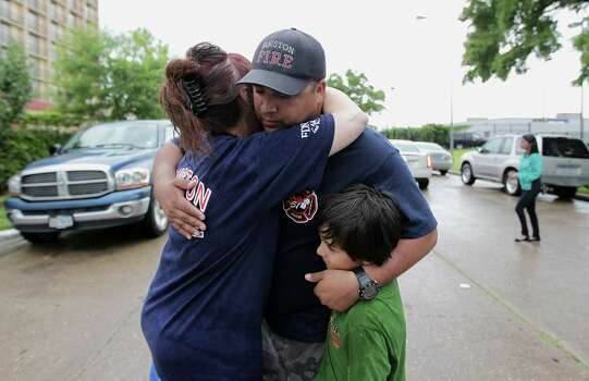 Patty Terry left, hugs Houston Fire Department station 51 firefighter George Saldana, Sr. center, as Saldana holds his son George Saldana, Jr. after to a prayer service at the scene of Friday's deadly fire which claimed the lives of four Houston Fire Department firefighters Sunday, June 2, 2013, in Houston. (AP Photo/Houston Chronicle, James Nielsen) Photo: James Nielsen, Associated Press / Houston Chronicle