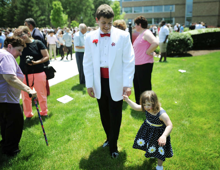 Graduate Jack Rende, of Trumbull, walks in the grass with his little sister, Samantha, 3, following Commencement Exercises at Fairfield Prep in Fairfield, Conn. on Sunday, June 2, 2013. Photo: Brian A. Pounds / Connecticut Post