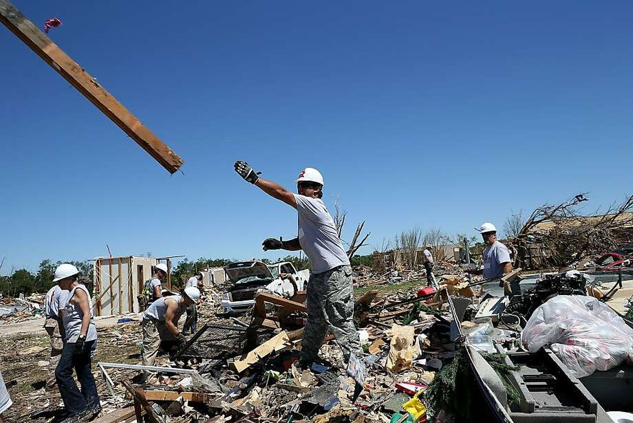 MOORE, OK - JUNE 02: Workers with Team Rubicon sift through the remains of a home that was damaged by a tornado on June 2, 2013 in Moore, Oklahoma. Residents of Moore, Oklahoma continue to recover and sift through the remains of their homes two weeks after a devastating EF-5 tornado ripped through the town killing 24 people and destroying hundreds of homes and businesses. (Photo by Justin Sullivan/Getty Images) Photo: Justin Sullivan, Getty Images