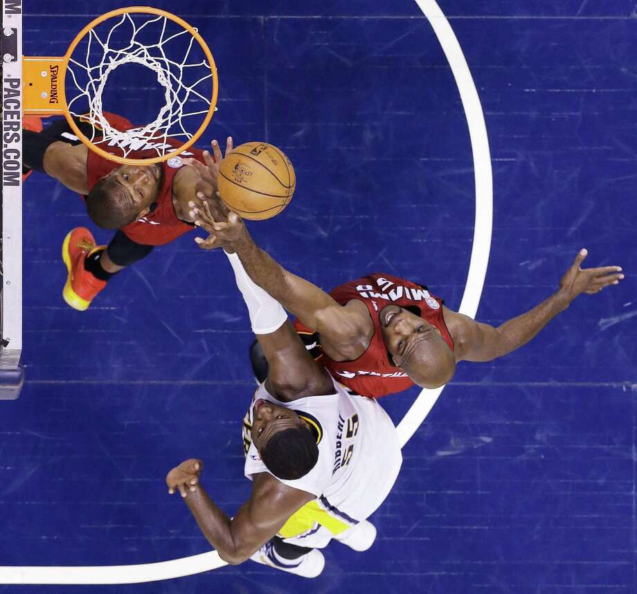 Miami Heat guard Dwyane Wade, left, takes a shot against Indiana Pacers center Roy Hibbert (55) as Miami Heat center Joel Anthony defends against Hibbert during the first half of Game 6 of the NBA Eastern Conference basketball finals in Indianapolis, Saturday, June 1, 2013. (AP Photo/Michael Conroy) Photo: Michael Conroy