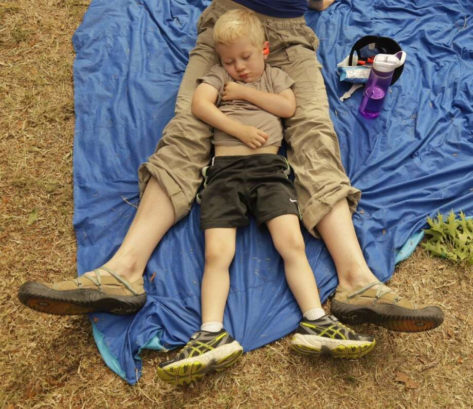 Three-year-old Gus Swanson takes a nap with his mom, Sarah Swanson, during the Cat Power show. (Todd Spoth/For the Chronicle)