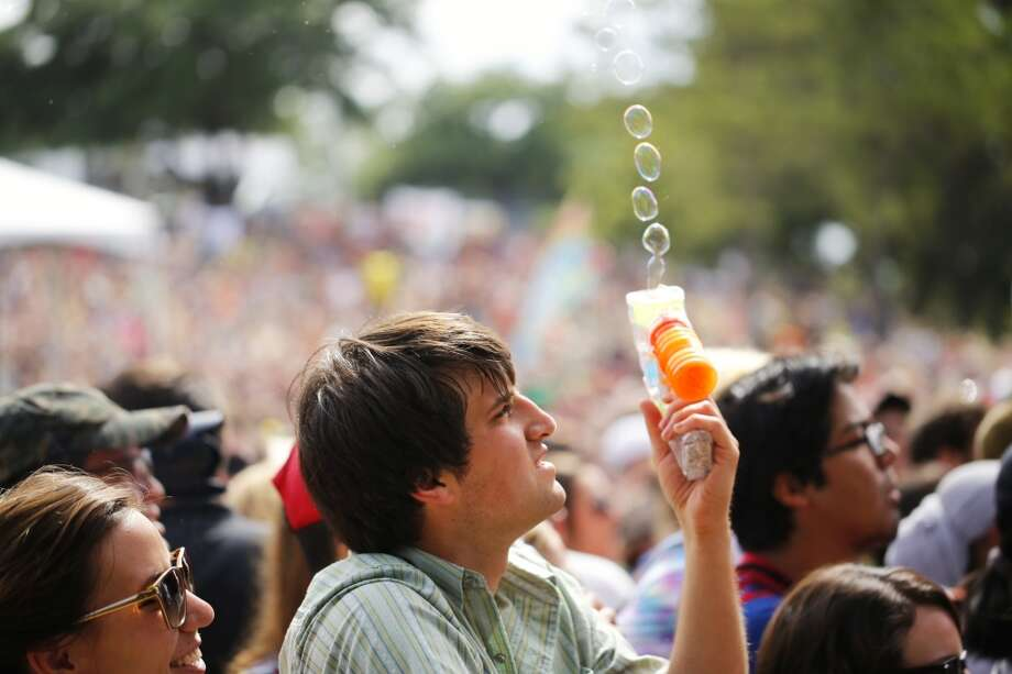 Wayland Christensen blows bubbles in the crowd during the Cat Power show.  (Todd Spoth/For the Chronicle)