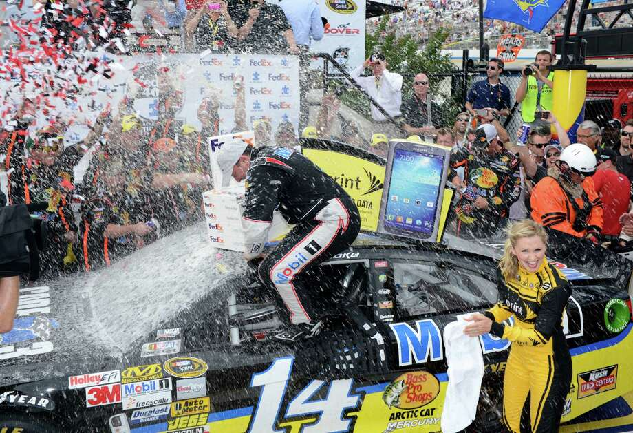 Tony Stewart is showered as he climbs out of the car to celebrate in Victory Lane after winning the NASCAR Sprint Cup Series auto race, Sunday, June 2, 2013, at Dover International Speedway in Dover, Del. (AP Photo/Nick Wass) Photo: Nick Wass