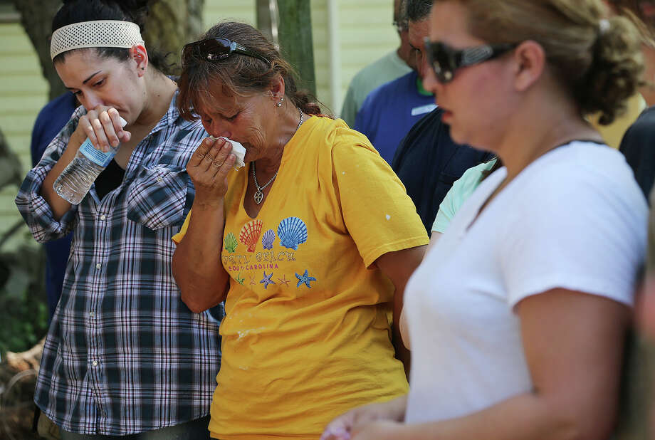 Gina Arellano, center, reacts as she and other flood-affected residents of Mission Road gather with members of Espada/Cabrini ACTS ministry for prayer, Sunday, June 2, 2013. The area flooded on May 25 after a record amount of rainfall fell throughout the city. Recovery efforts are underway along Mission Road but residents still have questions as to the cause of the flooding. Photo: JERRY LARA, San Antonio Express-News / © 2013 San Antonio Express-News