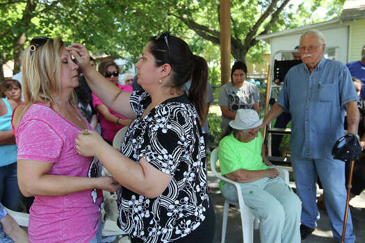 Brenda Barajas, 31, center, anoints her sister, Sandy Martinez, 49, left, as family of the flood-affected Mission Road gather with members of the Espada/Cabrini ACTS ministry to recite the Devine Mercy Chaplet, Sunday, June 2, 2013. The area flooded on May 25 after a record amount of rainfall fell throughout the city. Recovery efforts are underway along Mission Road but residents still have questions as to the cause of the flooding that displaced more than 50 residents. Photo: Jerry Lara, San Antonio Express-News / San Antonio Express-News