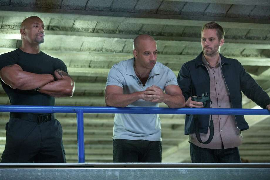 """This film publicity image released by Universal Pictures shows Dwayne Johnson , left, Vin Diesel, center, and Paul Walker in a scene from """"Fast & Furious 6."""" (AP Photo/Universal Pictures, Giles Keyte) Photo: Giles Keyte"""