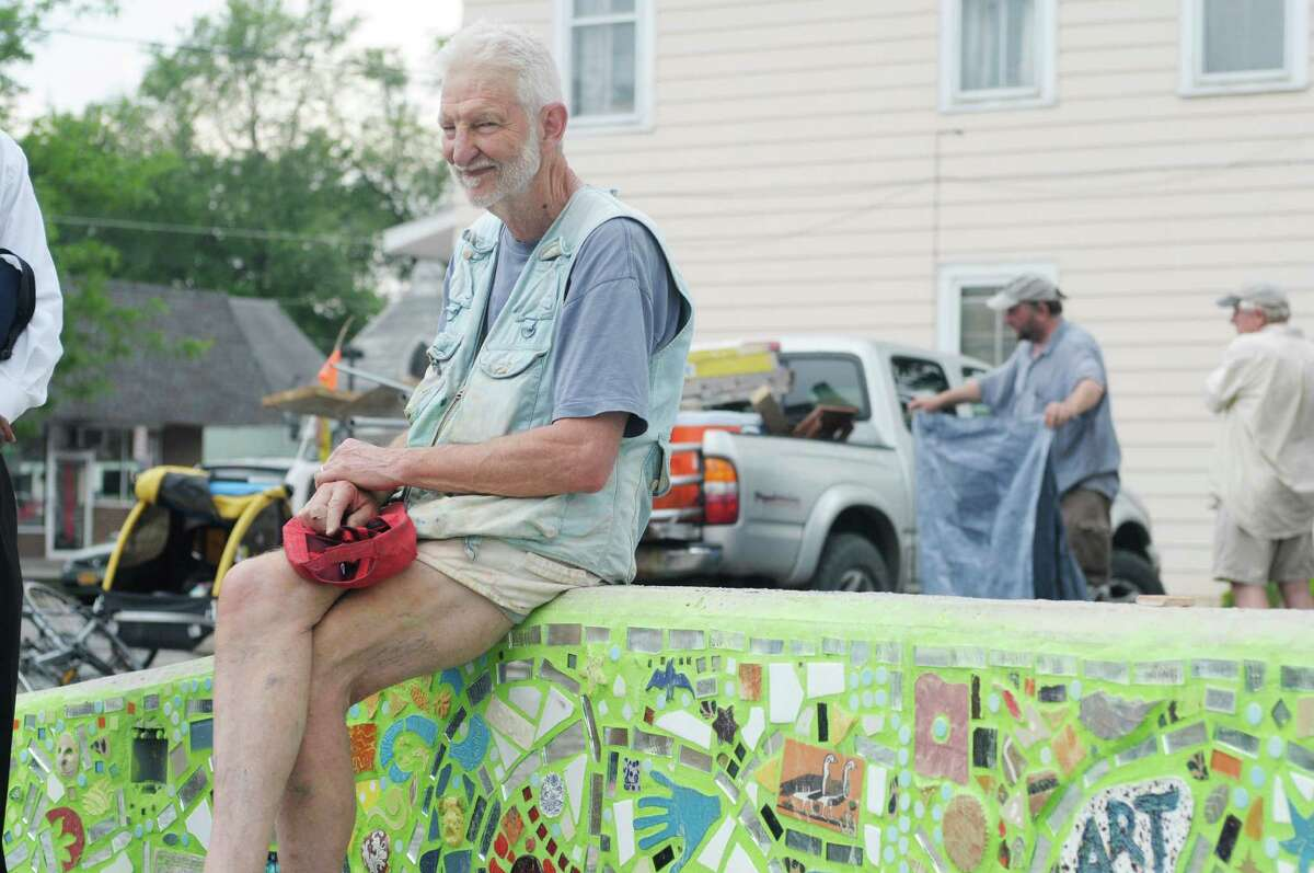 Mosaic artist, Isaiah Zagar from Philidelphia, PA, sits on the stage at the Freedom Square Art Stage on Sunday, June 2, 2013 in Troy, NY. The creation of the art stage and mosaic wall is a project being organized by the Media Alliance. The alliance brought in Zagar, who worked with the community members building the mosaic on Saturday and Sunday. The first musical concert on the stage will be held on June 15th, with a ceremony honoring those who took part in building the mosaic. The Media Alliance is planning various community art projects for the summer. (Paul Buckowski / Times Union)