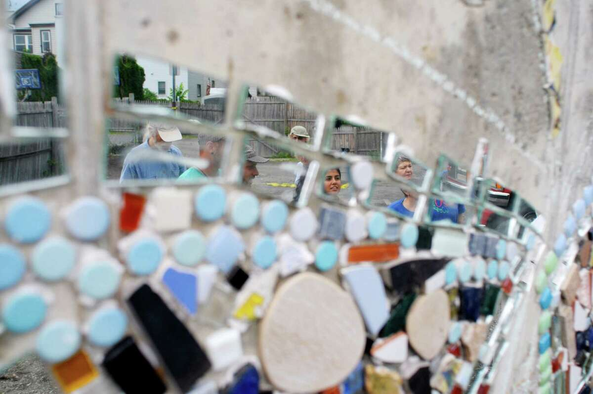 Community members are reflected in parts of the mosaic artwork at the Freedom Square Art Stage on Sunday, June 2, 2013 in Troy, NY. The creation of the art stage and mosaic wall is a project being organized by the Media Alliance. The alliance brought in mosaic artist, Isaiah Zagar from Philidelphia, PA, who worked with the community members building the mosaic on Saturday and Sunday. The first musical concert on the stage will be held on June 15th, with a ceremony honoring those who took part in building the mosaic. The Media Alliance is planning various community art projects for the summer. (Paul Buckowski / Times Union)