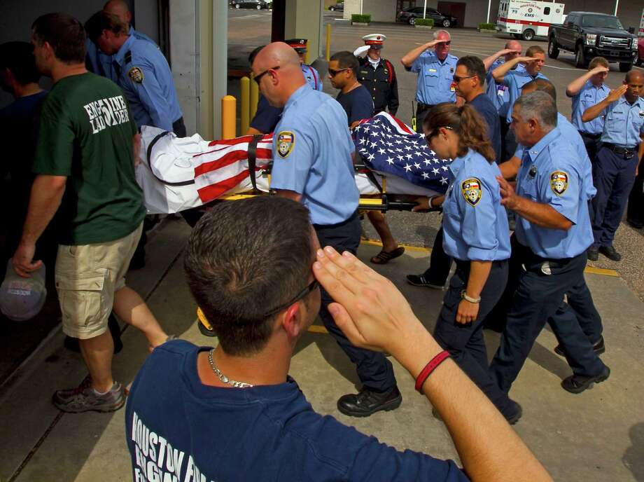 Houston Fire Department firefighters move the body of a fellow firefighter who was one of four firefighters that died in a 5 alarm hotel fire to the Robert H. Foley Funeral Home Sunday, June 2, 2013, in Houston. Photo: James Nielsen, Houston Chronicle / © 2013  Houston Chronicle