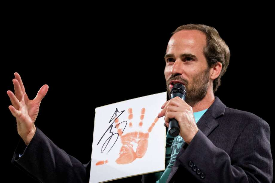 Host Andrew Freund presents the crowd with a sumo-themed keepsake between rounds of LivingSocial's Sumo + Sushi tour Sunday, June 2, 2013, at Fremont Studios in the Fremont neighborhood of Seattle. Each date of the eight-city tour includes a three-course sushi meal and sake for attending guests. Photo: JORDAN STEAD, SEATTLEPI.COM / SEATTLEPI.COM