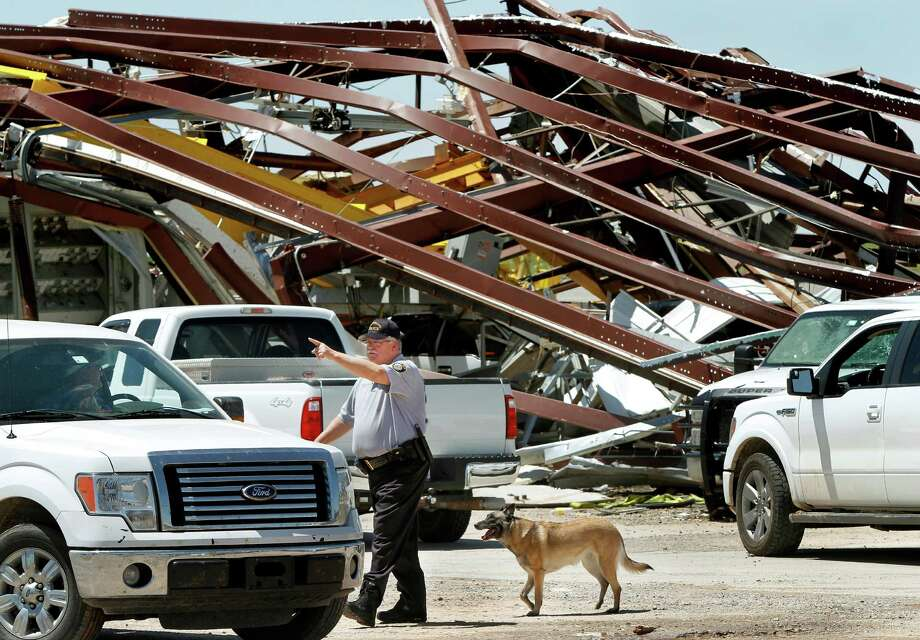 A police officer offers directions to a driver leaving this heavily damaged supply yard for Cactus Drilling Company on State Highway 66 in El Reno, Okla. on Saturday, June 1, 2013. Employee David Stottemyre was working in the lot when the tornado took aim at the plant. Stottemyre ran inside the large supply storage building and took shelter as the tornado passed over, leaving the building in a twisted pile of steel and metal. He was not injured. (AP Photo/The Oklahoman, Jim Beckel) LOCAL STATIONS OUT (KFOR, KOCO, KWTV, KOKH, KAUT OUT); LOCAL WEBSITES OUT; LOCAL PRINT OUT (EDMOND SUN OUT, OKLAHOMA GAZETTE OUT) TABLOIDS OUT Photo: Jim Beckel