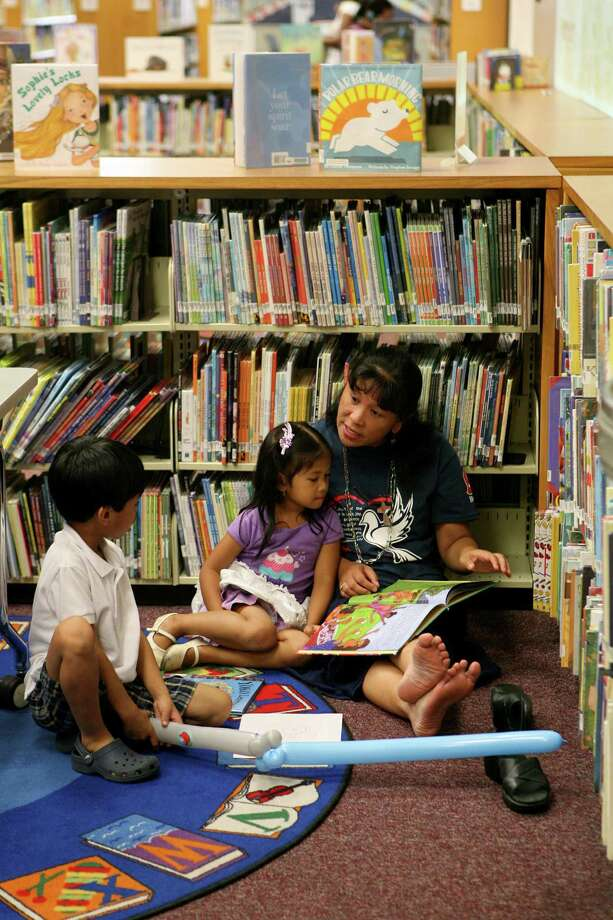 Catherine Cuasay reads to her daughter, Adira, as Pelle Cuasay listens and plays with his balloon during Westfall Library's 50th anniversary celebration. Photo: Cynthia Esparza / For The Express-News