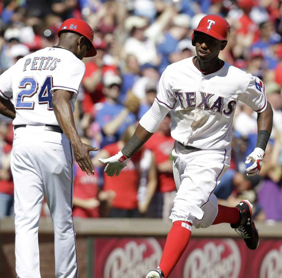 Rangers rookie Jurickson Profar (right) circles the bases after his solo home run in the eighth inning broke a 1-1 tie. Profar hit his second homer in 10 games after his May 19 call-up. Photo: LM Otero / Associated Press