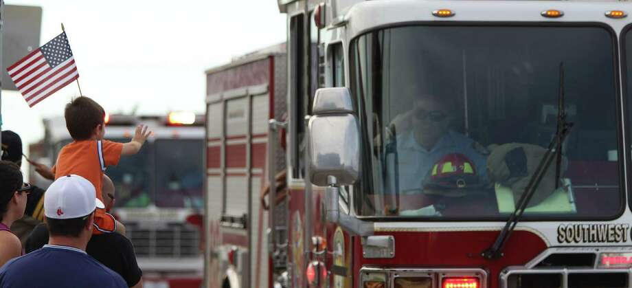 Ethin Waguespack, 4, waves to a fire truck from the shoulder of his father, Eric Waguespack, as they watch  the procession for Robert Bebee, a longtime friend. Photo: Karen Warren, Staff / © 2013 Houston Chronicle