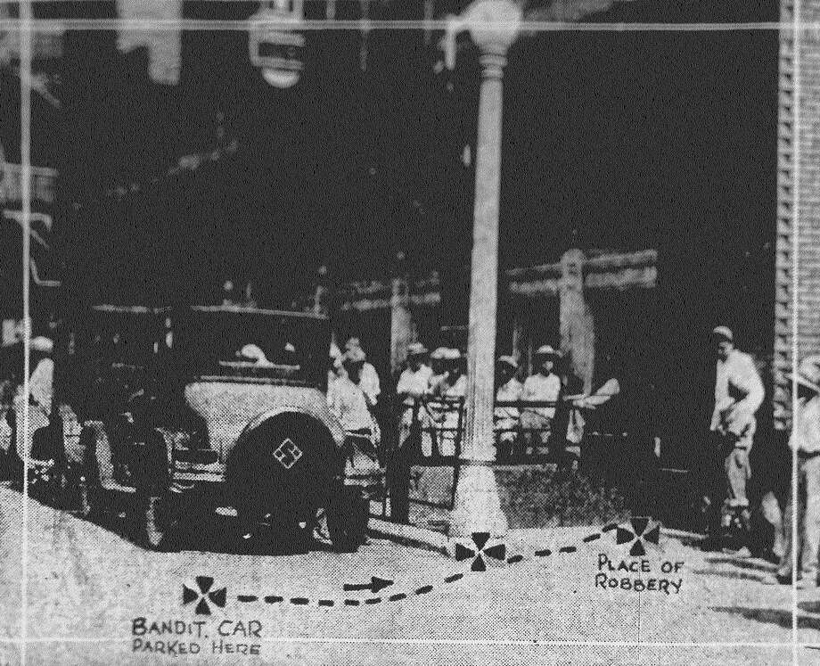 Defying the law in the heart of downtown San Antonio, three bandits took $6,736.68 in payroll from B.F. Farmer, cashier of the Light Publishing Co., and Gerald J. Myers, bookkeeper, and made their escape. The photo illustrates how the daring daylight robbery was executed. Cross at left shows where bandit car was parked. Two men waited in the car while a third accosted Farmer and Myers near the lamp post. Threatened with a pistol, they were backed a few feet against the Light building and the bag containing the money was taken from them. Published in the San Antonio News June 26, 1928. Photo: File Photo